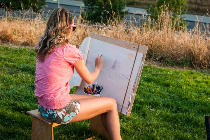 girl drawing outdoors at an easel