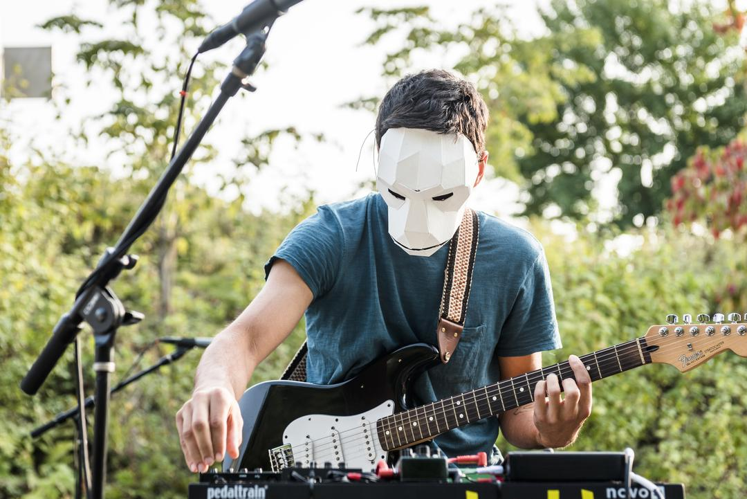 Photo of a man playing guitar while wearing a paper mask, folded to look like a monkey face.
