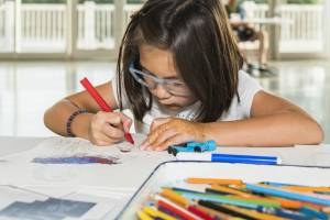 Photo of a young girl in glasses coloring at a table in PACCAR Pavilion.